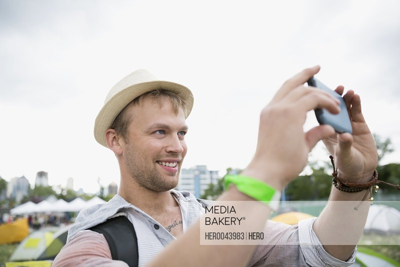 Young man taking selfie at summer music festival campsite