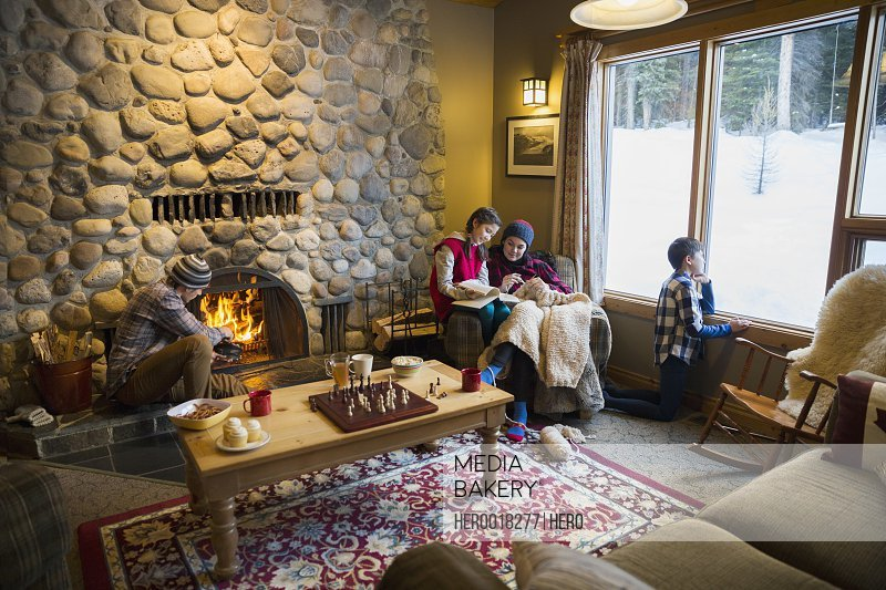 Family relaxing near fireplace in lodge living room