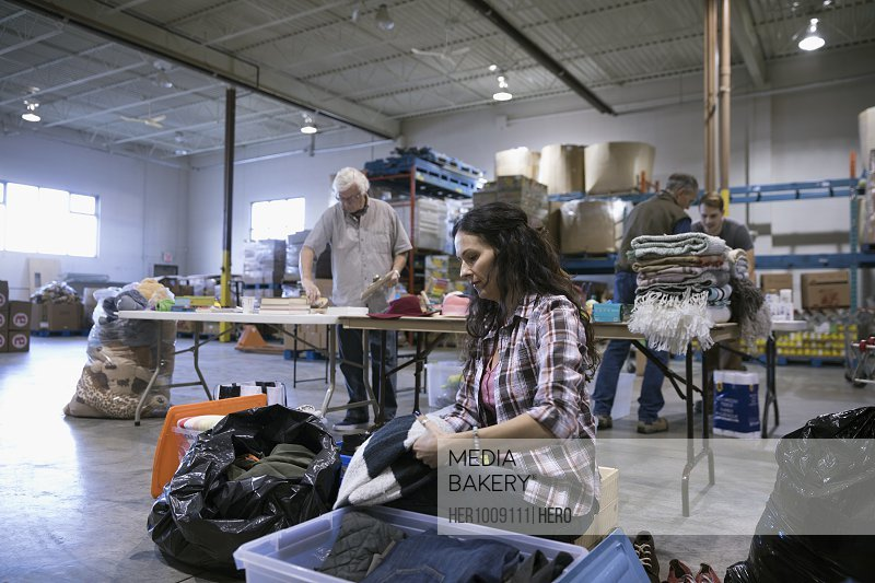 Female volunteer sorting clothing for clothing drive in warehouse