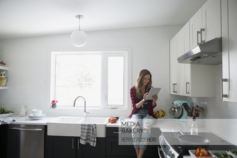 Woman using digital tablet on kitchen counter
