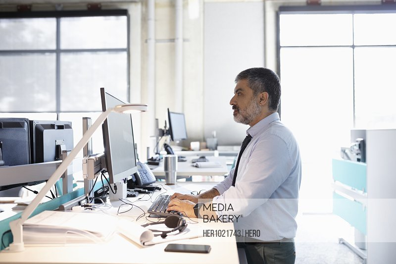 Businessman working at computer at sit-stand desk in open plan office