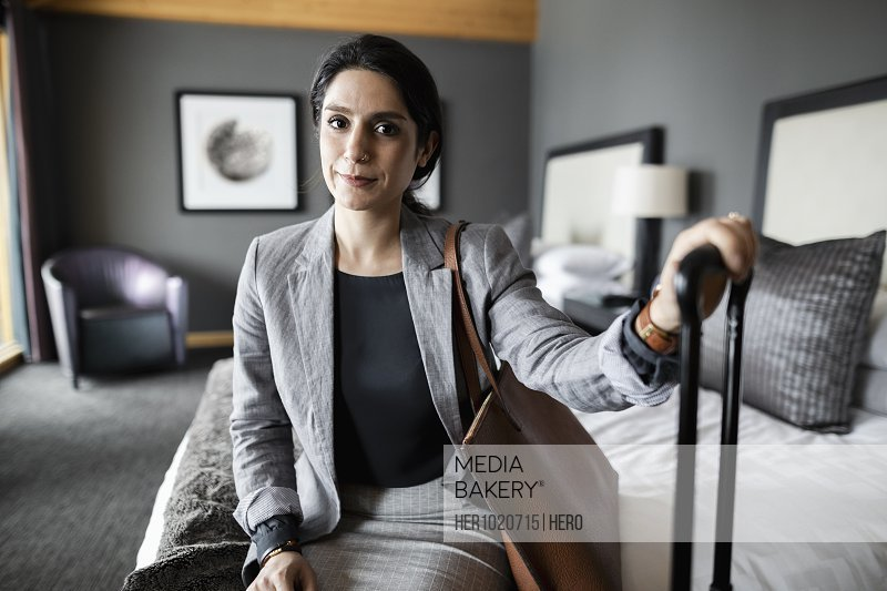 Portrait confident businesswoman sitting on bed in hotel room