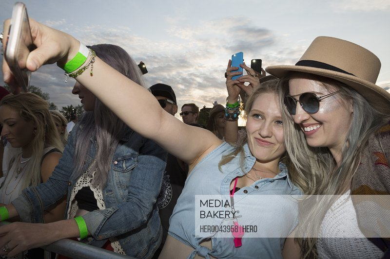 Young women taking selfie in crowd at summer music festival