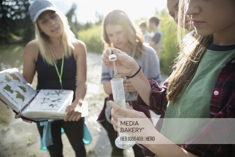 Female teacher and teenage girl outdoor school students conducting scientific experiment in nature