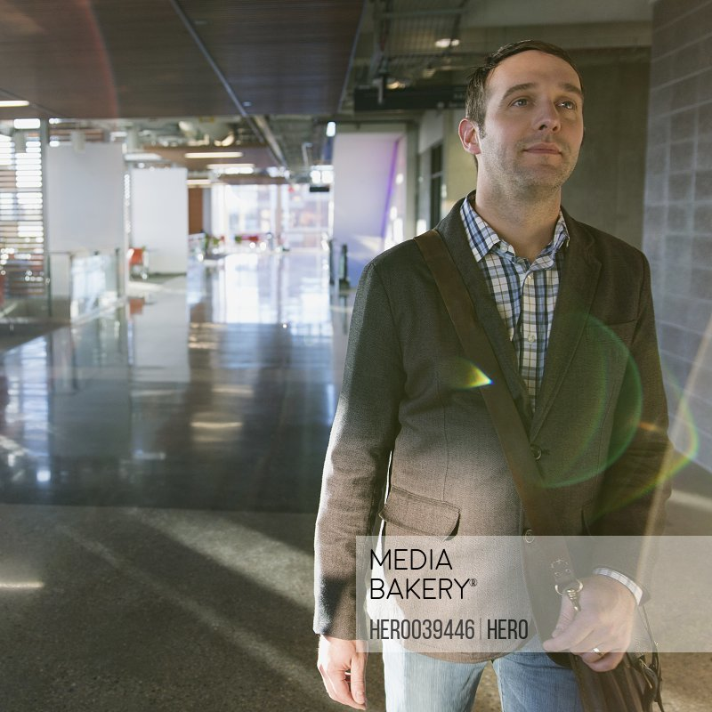 Businessman walking in hallway with briefcase
