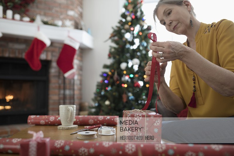 Mature woman wrapping Christmas gifts, cutting ribbon in living room