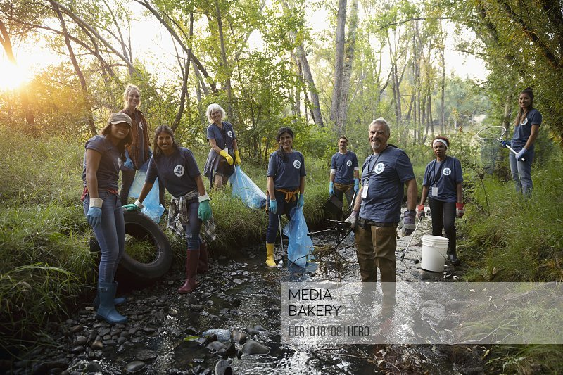 Portrait confident people volunteering, cleaning up garbage in stream