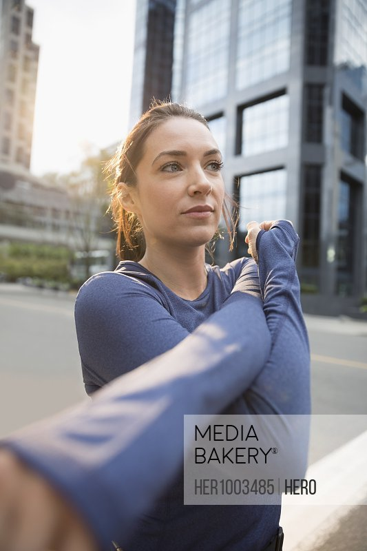 Young female runner stretching arm on urban street