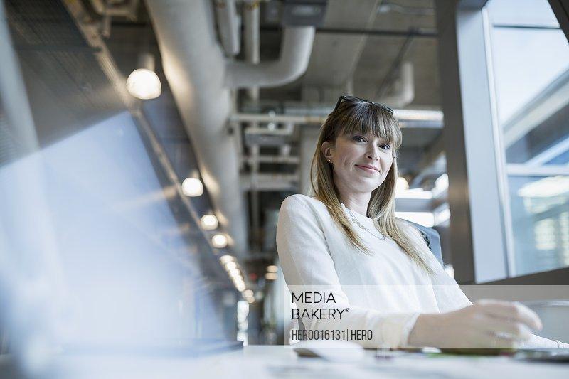 Portrait of confident businesswoman at office desk
