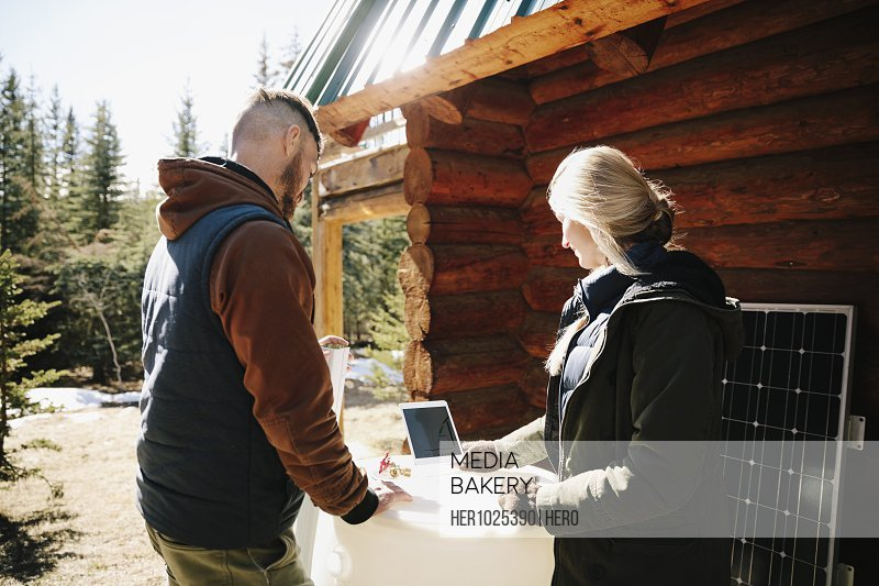 Couple with digital tablet installing rain barrel