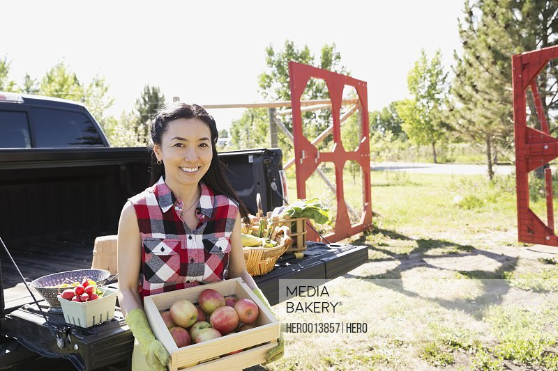 Woman holding box of apples outside truck