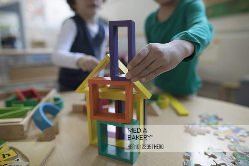 Preschool girl and boy playing with building blocks in classroom