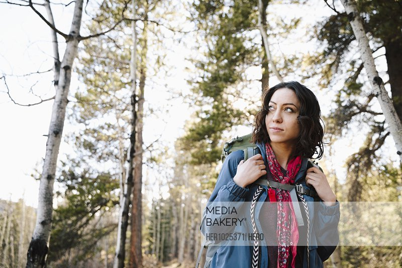 Portrait confident woman with backpack hiking in woods