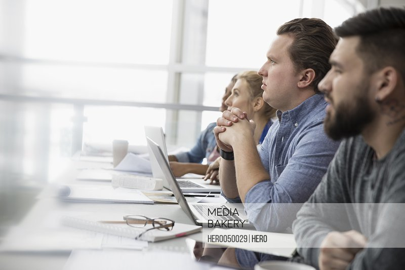 Serious attentive business people listening in meeting