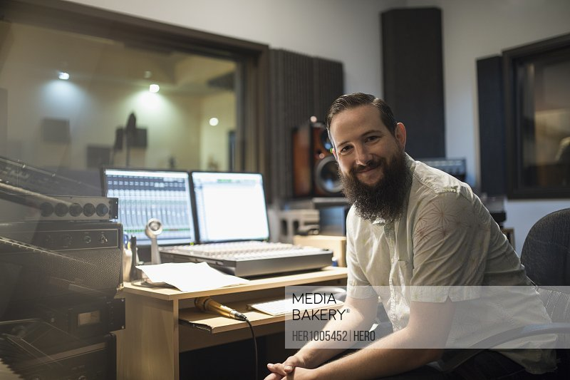 Portrait confident male music producer in recording studio