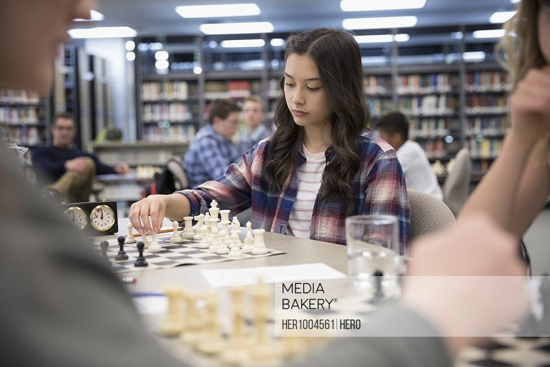 Focused girl middle school student playing chess in chess club library