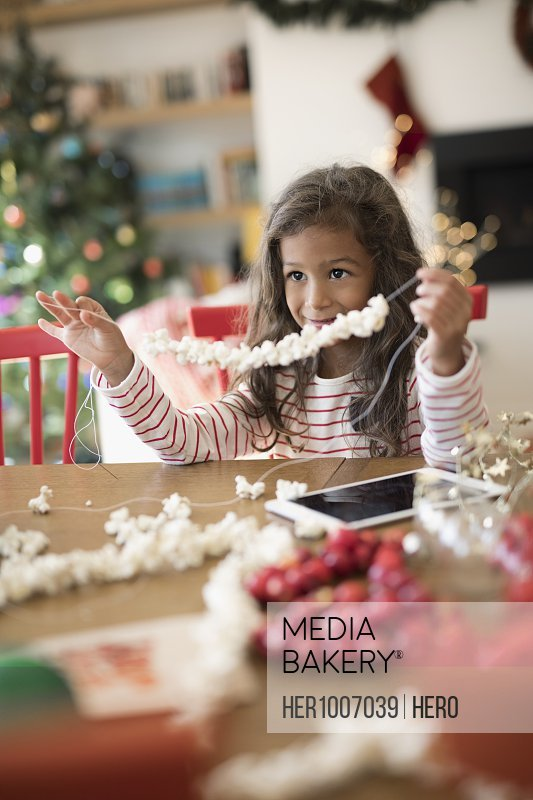 Smiling girl stringing popcorn Christmas decoration at table
