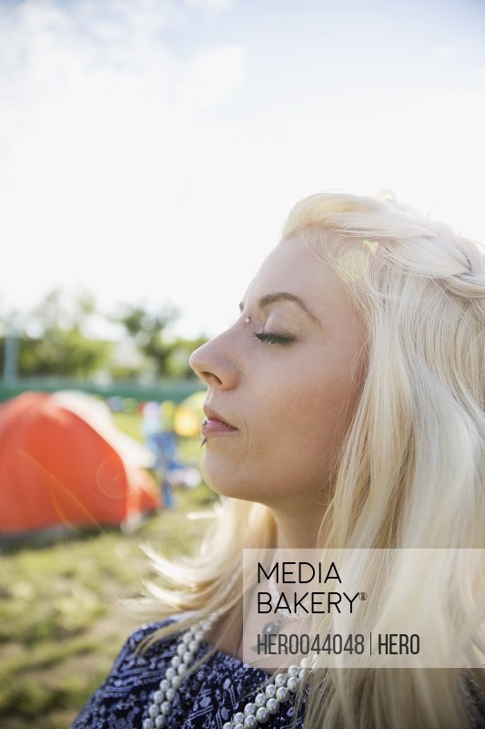 Profile portrait serene young woman relaxing at summer music festival campsite