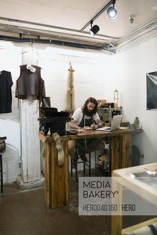 Leather shop owner entrepreneur working at laptop