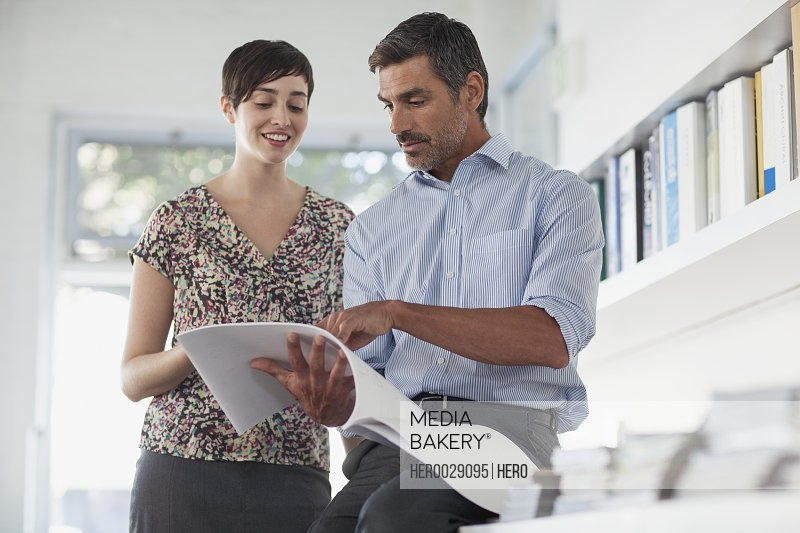 businessman and businesswoman reviewing paperwork in their office