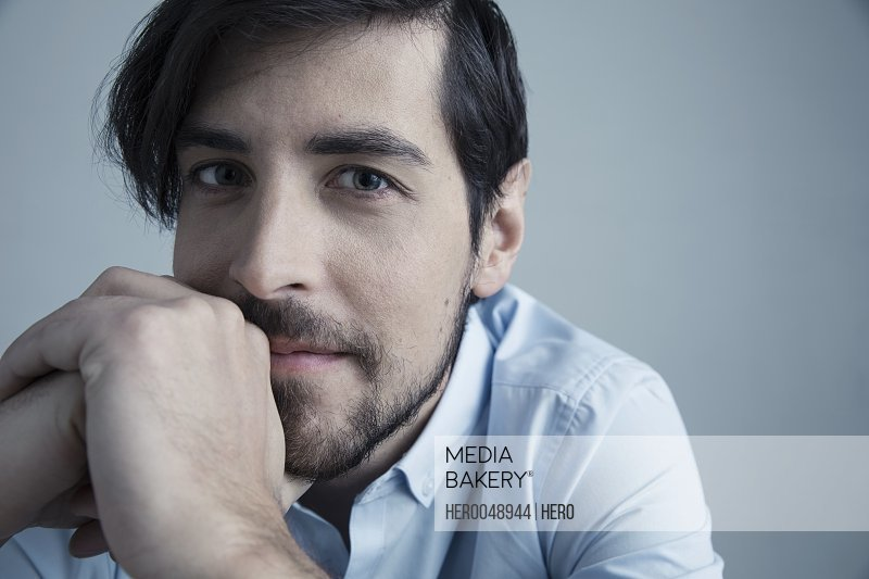 Close up portrait confident brunette Caucasian man with beard and hands clasped
