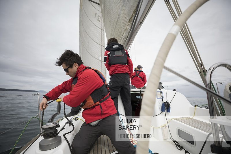Sailing team adjusting rigging and sail on sailboat