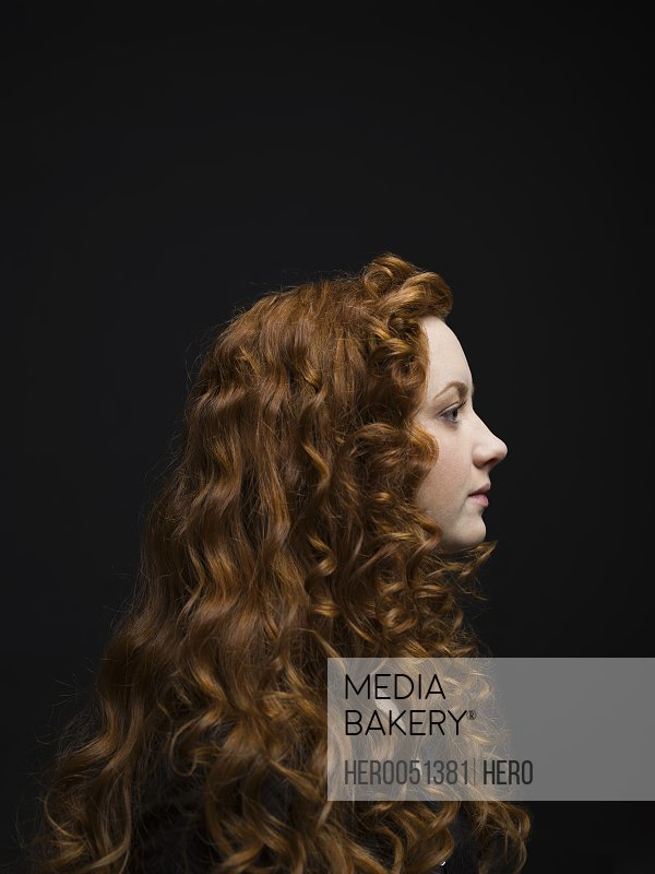 Profile portrait serious woman with long curly red hair against black background