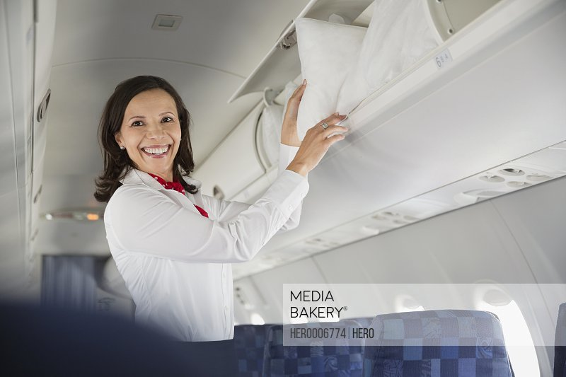 Flight attendant taking pillow out of overhead compartment in airplane