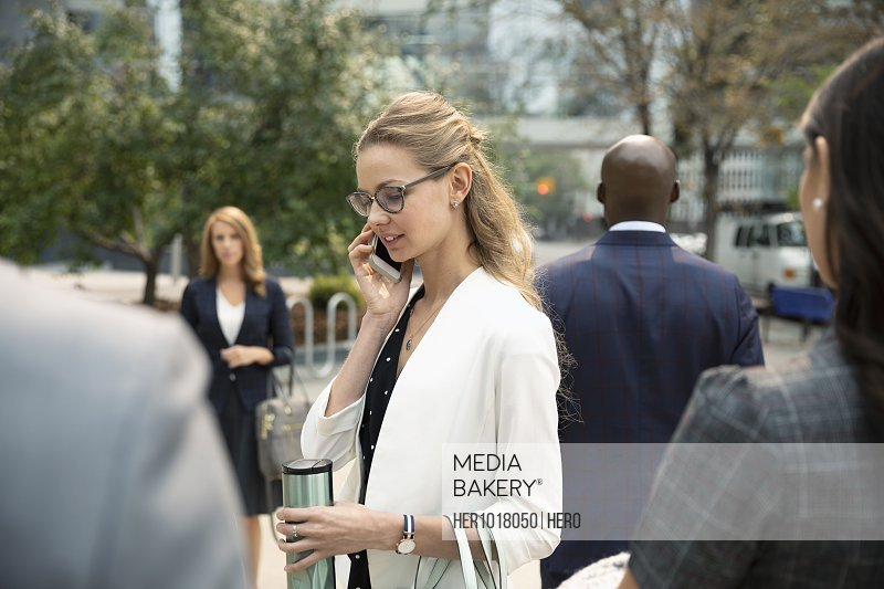 Businesswoman with coffee talking on smart phone on urban sidewalk