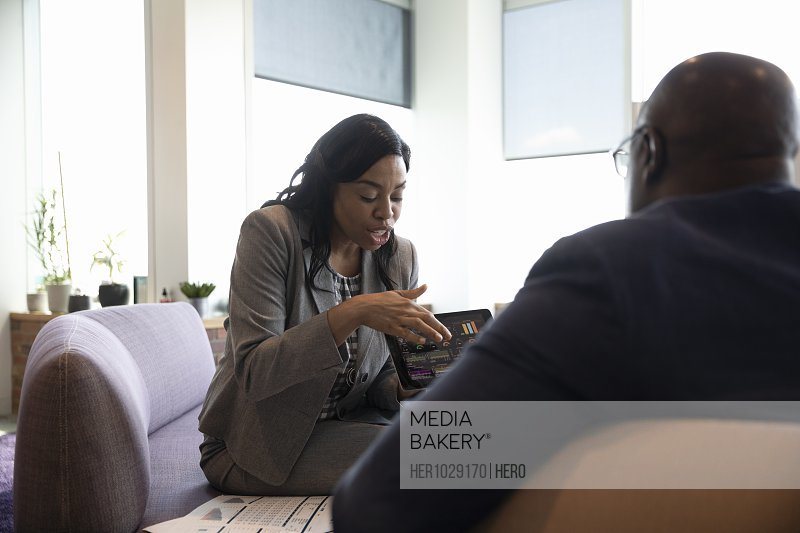 Businesswoman showing colleague digital tablet in office