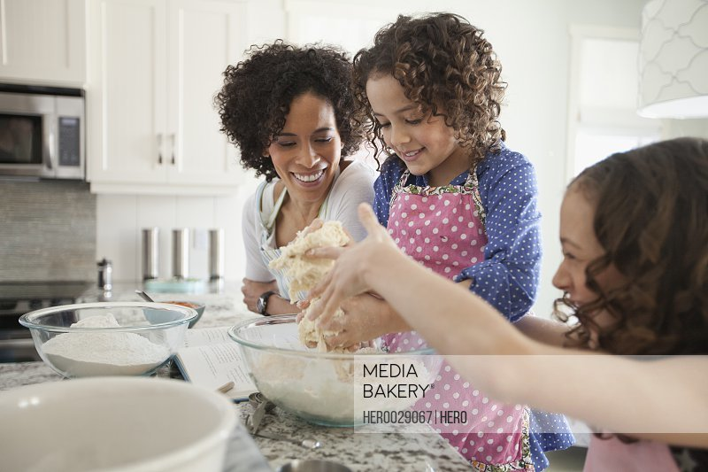 mom and young daughters baking