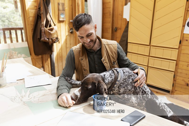 Male artist with dog at cabin table