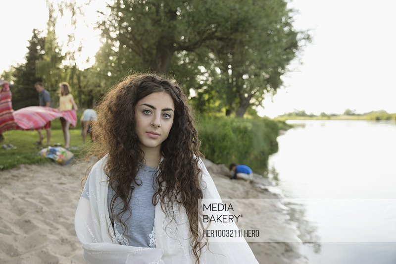 Portrait young woman wrapped in blanket on summer lakeside beach
