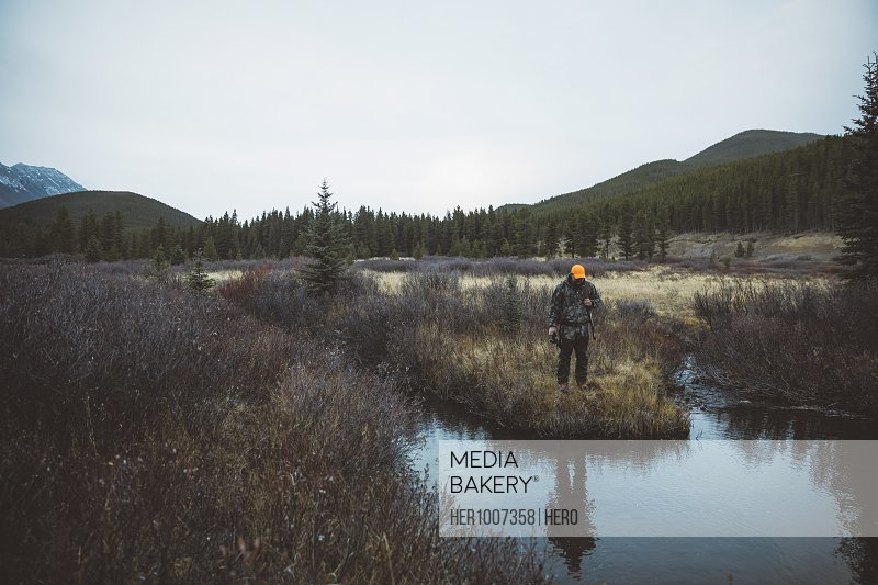 Male hunter tracking and hunting, looking down at water in remote field