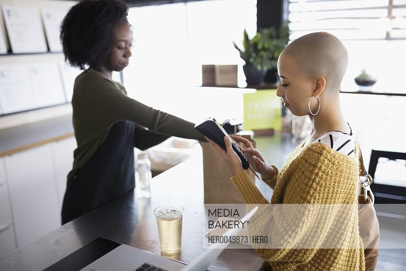 Young woman with shaved head using credit card reader at juice bar