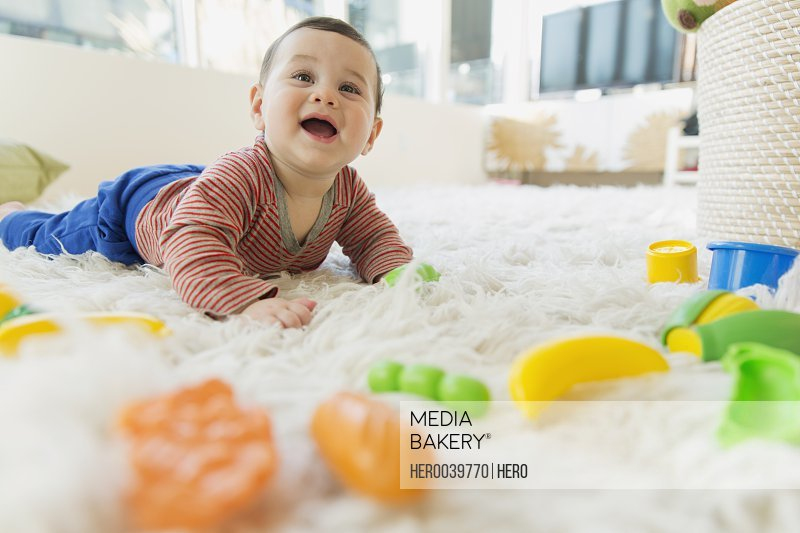 Baby lying on fuzzy rug with plastic toys