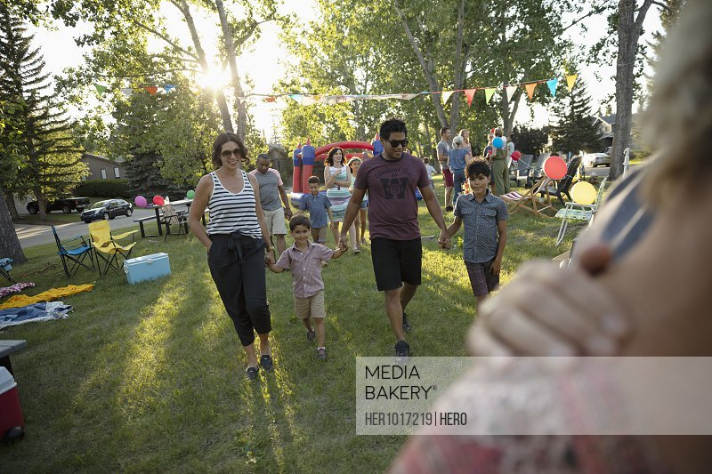 Family holding hands, walking at summer neighborhood block party in park