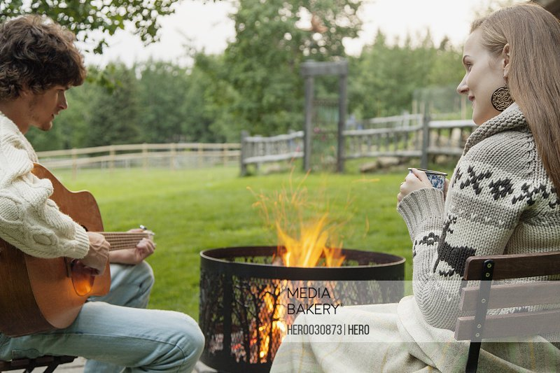 young adult couple sitting by a fire enjoying some guitar