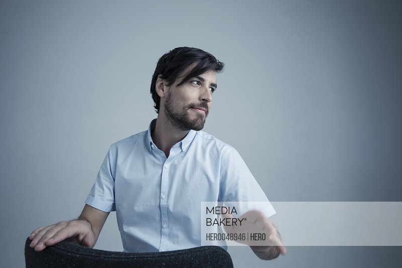Portrait cool brunette Caucasian man with beard gesturing with hand and looking away