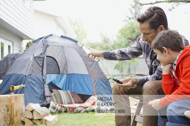 Father showing son compass while camping outside
