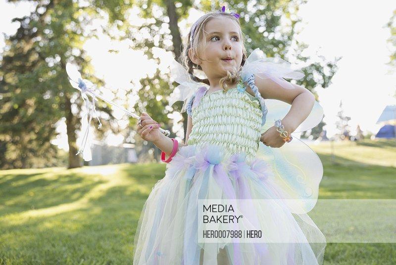 Cute girl wearing fairy costume outdoors