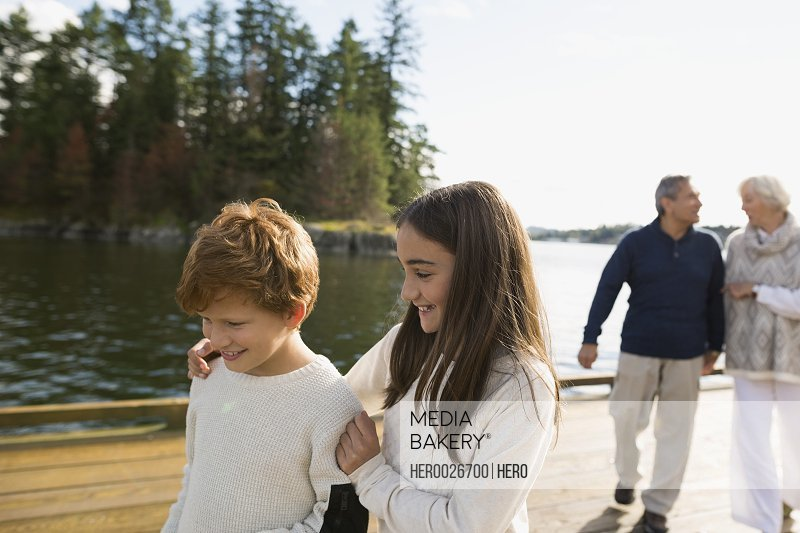 Sister hugging brother on lake dock