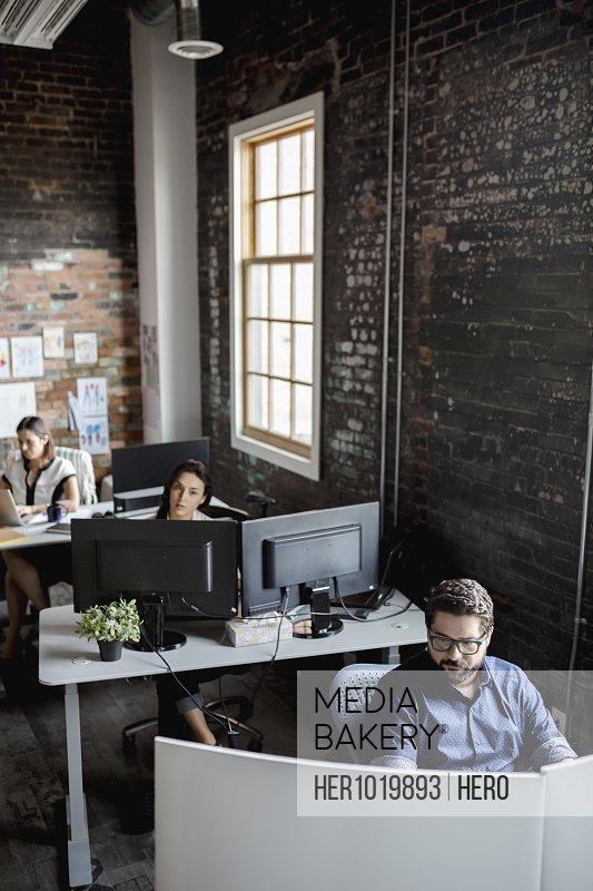 Creative business people working at desks in open plan loft office