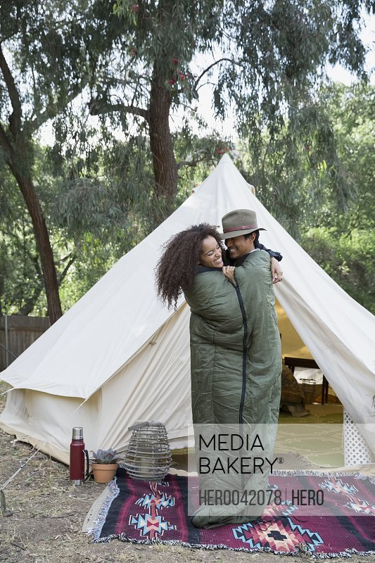 Playful couple sharing sleeping bag outside camping yurt