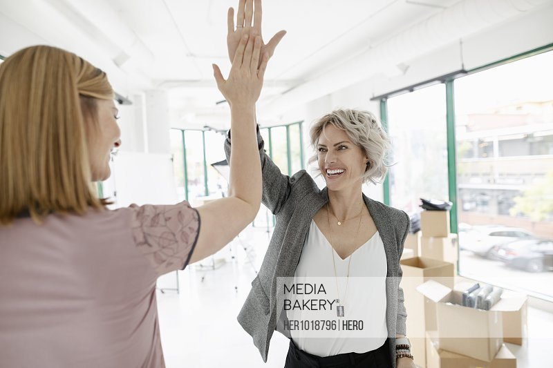 Excited female business owners high-fiving in new retail space