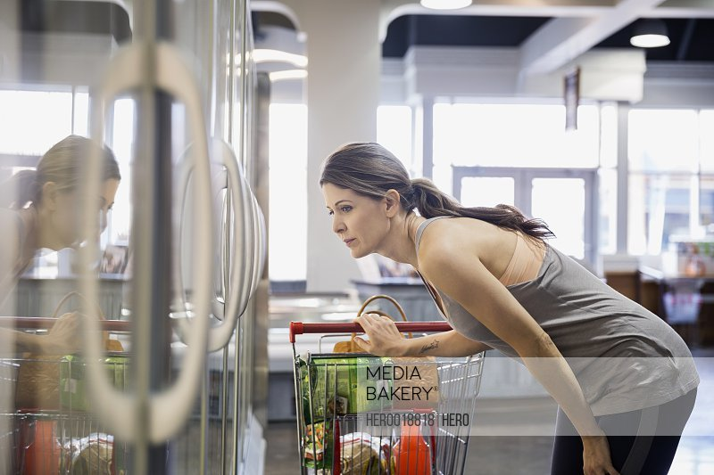 Woman shopping frozen foods in grocery store