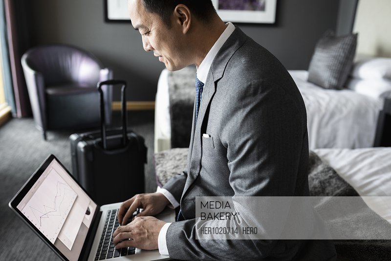 Businessman working at laptop in hotel room