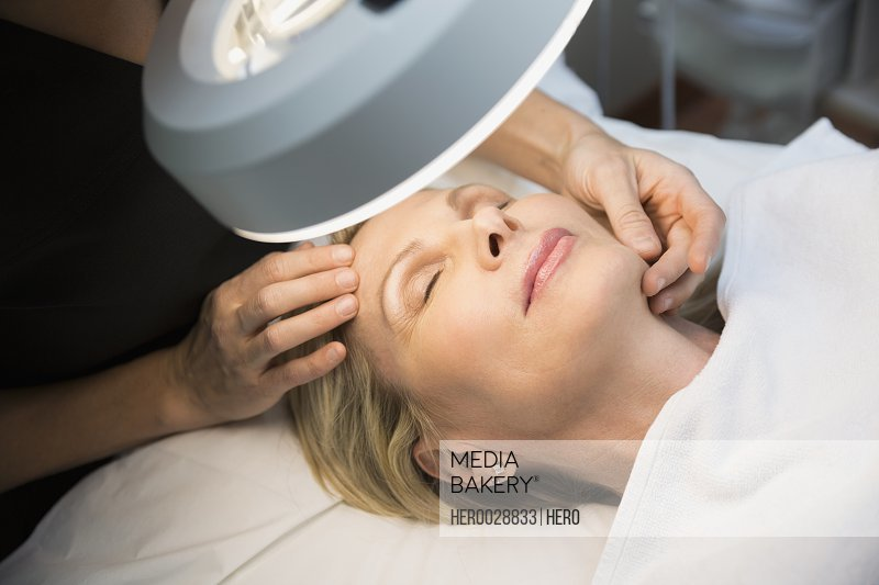 Aesthetic technician examining womans face under light