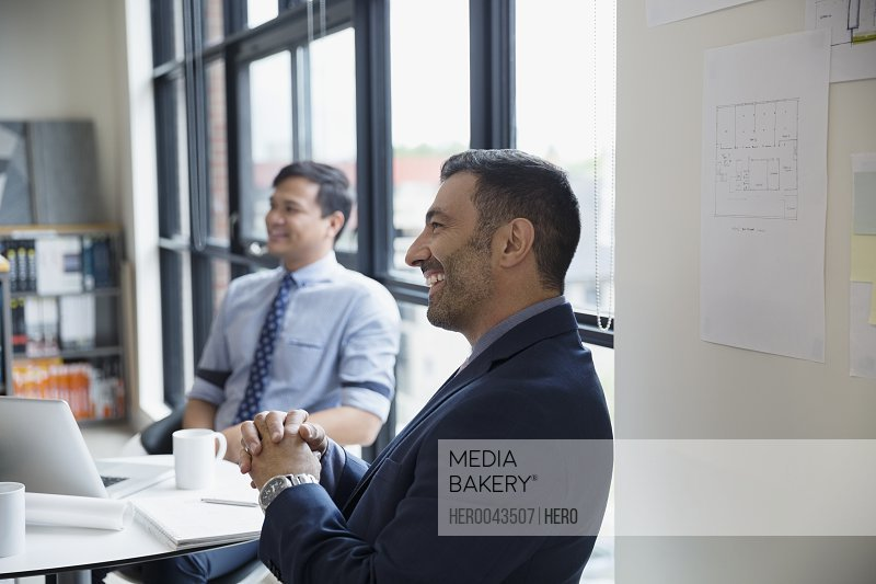 Smiling architects listening in meeting