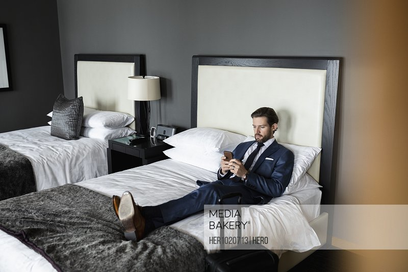 Businessman using smart phone on bed in hotel room